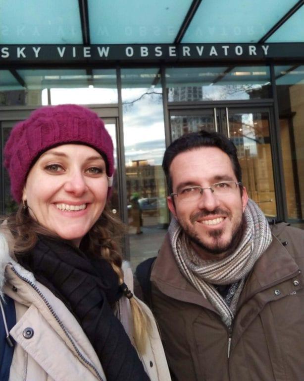 """Selfie da Chai e do Augusto em frente a porta do prédio onde se lê """"Sky View Observatory"""""""
