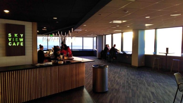 """Na esquerda o balcão do bar com a placa iluminada onde se lê """"Sky View Café"""" e na direita a parede de vidro com mesas altas."""