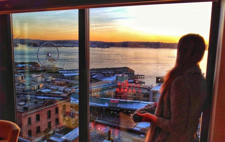 Chai olhando pela janela a vista da baía de Elliot onde se vê a roda gigante e o letreiro do Pike Place Market