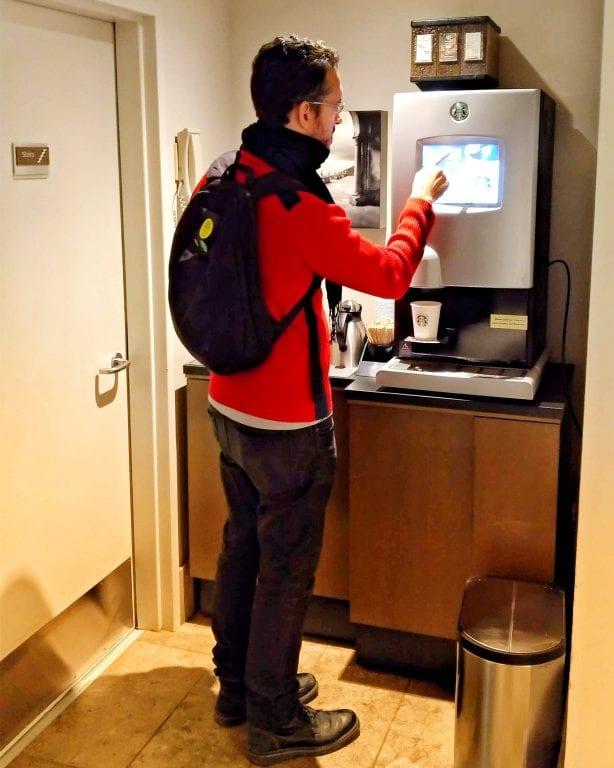 Augusto pegando um café na máquina de café da Starbucks do corredor do hotel
