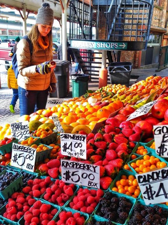 Chai está segurando a metade de uma laranja atrás de uma banca de frutas vermelhas no Pike Place Market de Seattle