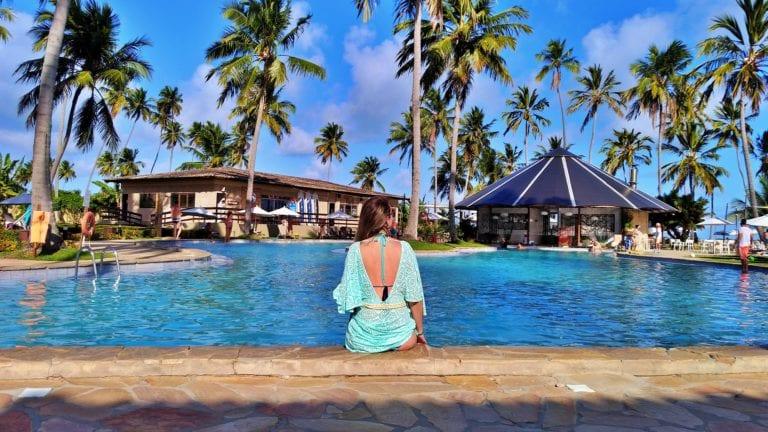 Chai no centro da foto sentada de costas na borda da piscina enorme de água azulzinha. No fundo dois prédios e os coqueiros contrastando no imenso céu azul