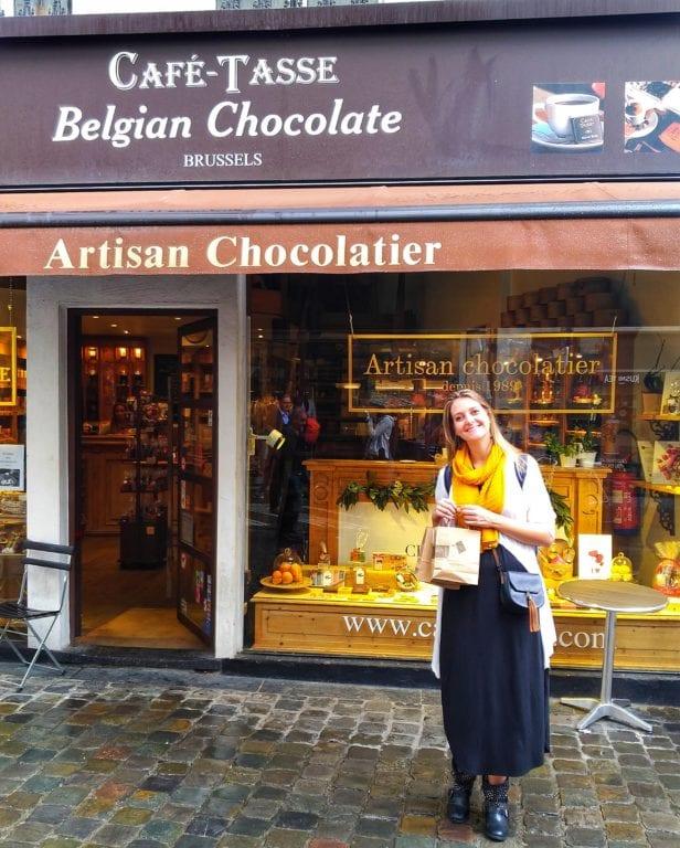 Chai em frente a loja segurando a sacola de papelão cheia de chocolates