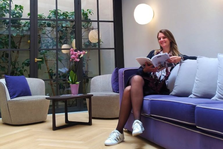 chai com lendo uma revista sentada no sofá confortável do jardim de inverno do Palazzo DiPinto