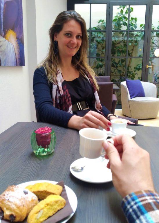 Onde ficar em Lucca. Um prato com croissant sobre a mesa ao lado do da mão do Guto segurando a xicara de café com a Chai ao fundo segurando sua xícara e sorrindo.