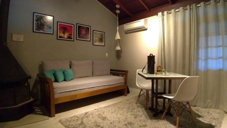 Sala de estar com sofá grande, lareira, televisão e um pequena mesa de refeições