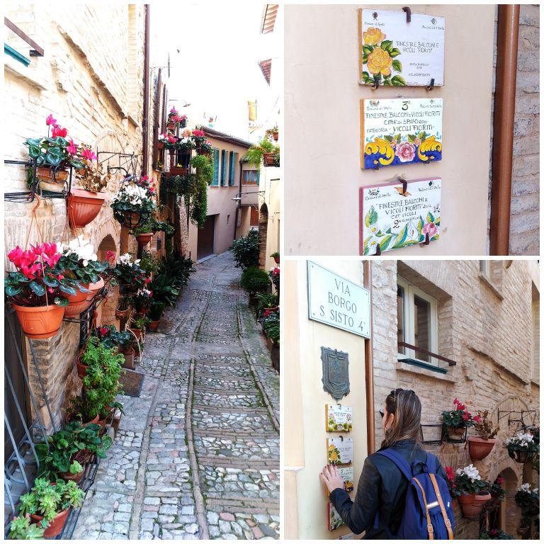 Sacadas e ruas floridas em Spello. Nas paredes, as placas das últimas premiações em uma das ruas mais premiadas.
