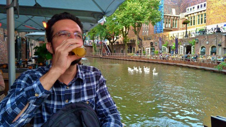Augusto de camisa xadrez está bebendo uma cerveja e ao fundo um canal onde um grupo de cisne nada tranquilamente