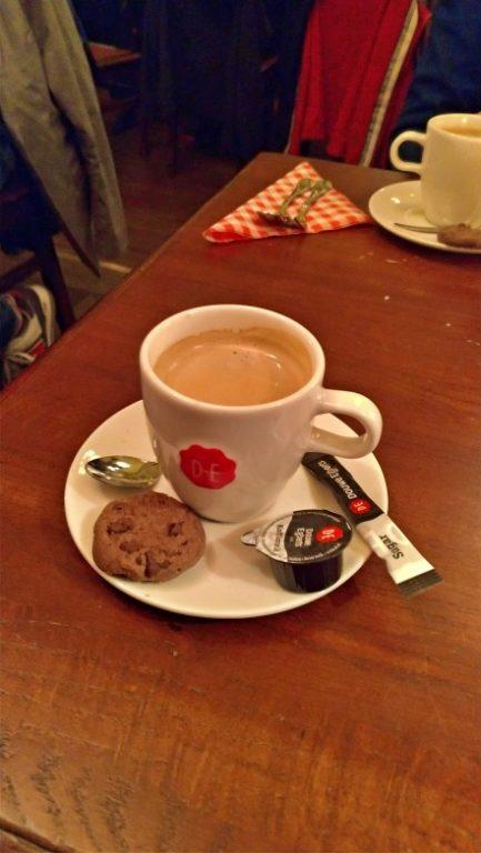Na foto uma xícara branca de café expresso com um biscoito, sachê de açúcar e potinho de leite no pires sobre a mesa de madeira. Belgisch Biercafé Olivier Utrecht