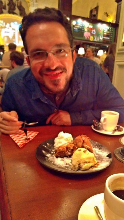 Na foto Augusto está sorrindo com a colher na mão aguardando para comer a fatia de torta de maça entre uma bola de sorvete e uma porção de chantili que está no prato a sua frente
