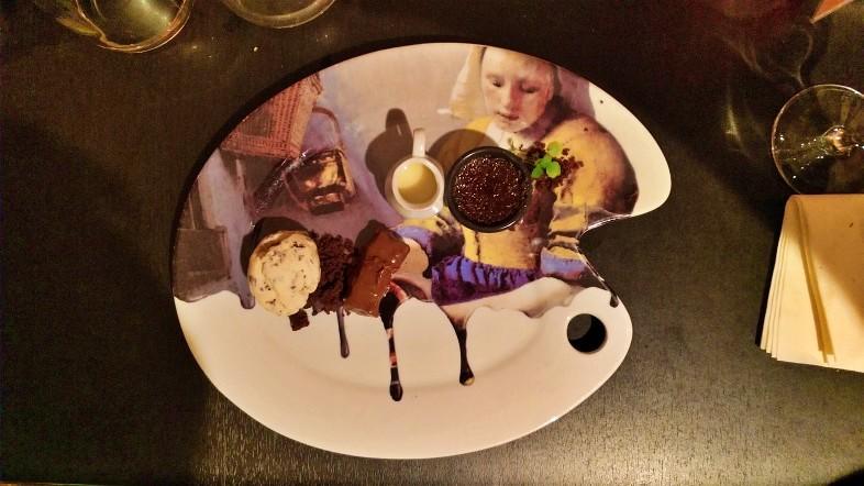 Prato de sobremesa visto de cima em formato de palheta de pintura com estampa da obra A Leiteira do pintor Veermer