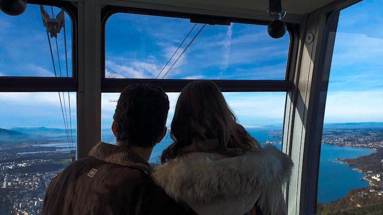 Guto e Chai de costas admirando De dentro do bondinho do Pfanderbahn, o teleférico da Montanha Pfander em Bregenz