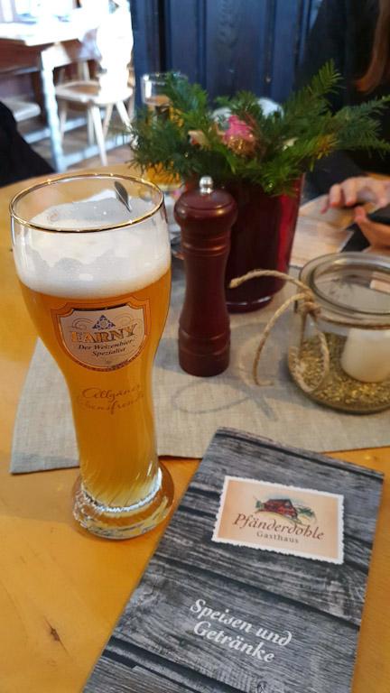 Copo de Weizenbier sobre a mesa no restaurante com utensílios e cardápio ao lado