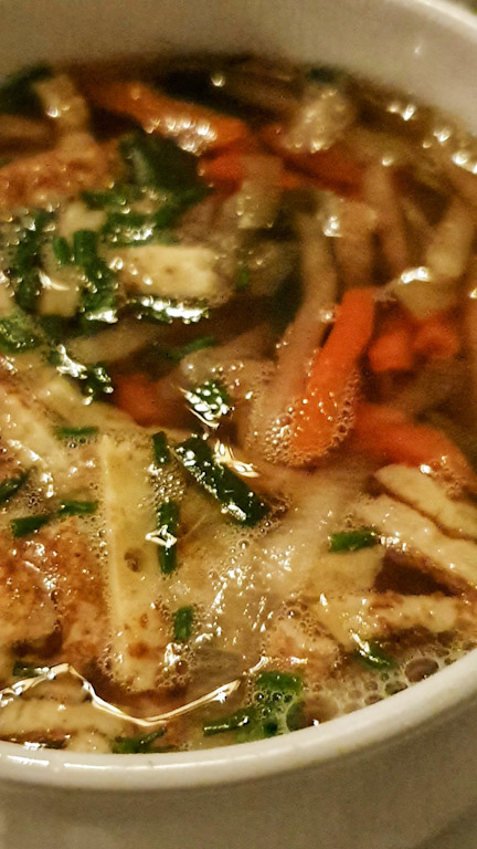 Gasthaus Goldener Hirschen: caldo da carne servido como uma sopa de entrada em uma tigela com fatias de panqueca.