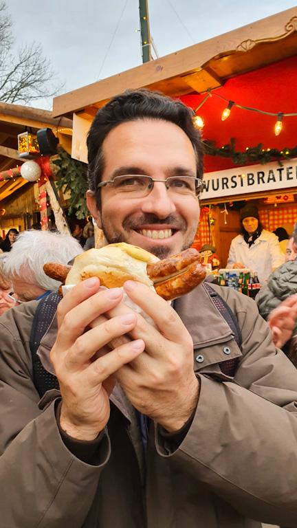 Augusto comendo uma bratwurst no Mercado de Natal de Lindau