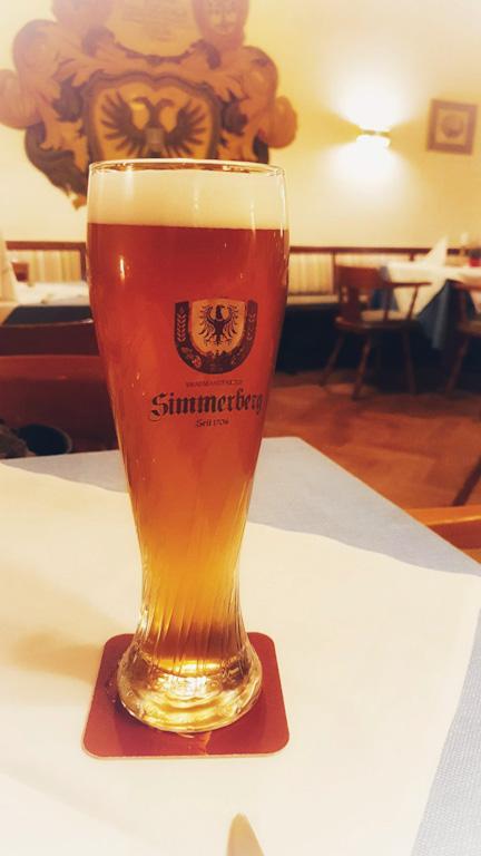 Copo de weizenbier (cerveja de trigo) sobre uma mesa de toalha branca no restaurante