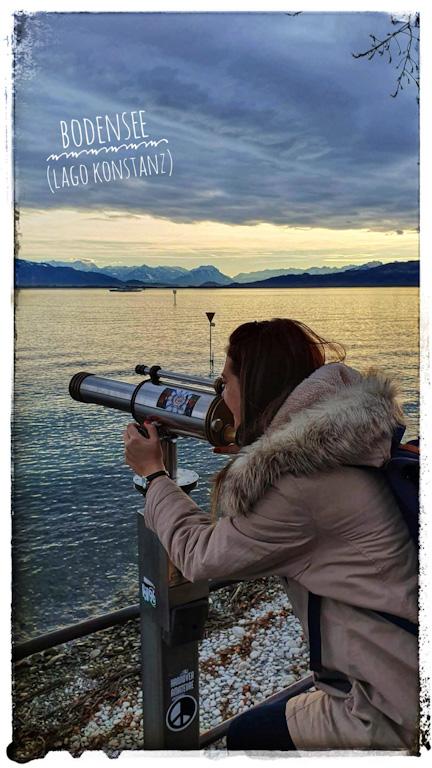 Chai olhando em um binóculo de chão à beira do Lago Constança com água refletindo a luz do entardecer e os alpes ao fundo