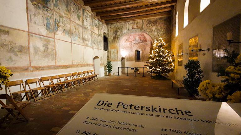 Vista interna da igreja com ângulo de câmera bem aberto mostrando a parede dos afrescos à esquerda e no fundo e a parede lateral direita com candelábros