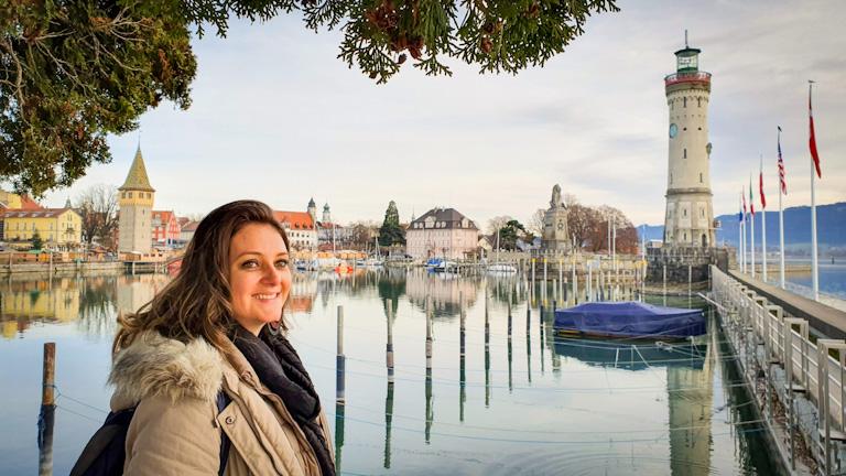 Chai quase de perfil em primeiro plano à esquerda sorrindo. Ao fundo o porto de Lindau onde se vê o novo farol, a estátua do leão bávaro que na entrada do porto e os demais prédios que circundam a enseada do porto.