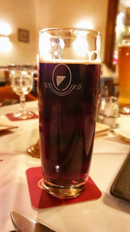 Copo de dunkel (cerveja de trigo escura) sobre uma mesa de toalha branca no restaurante