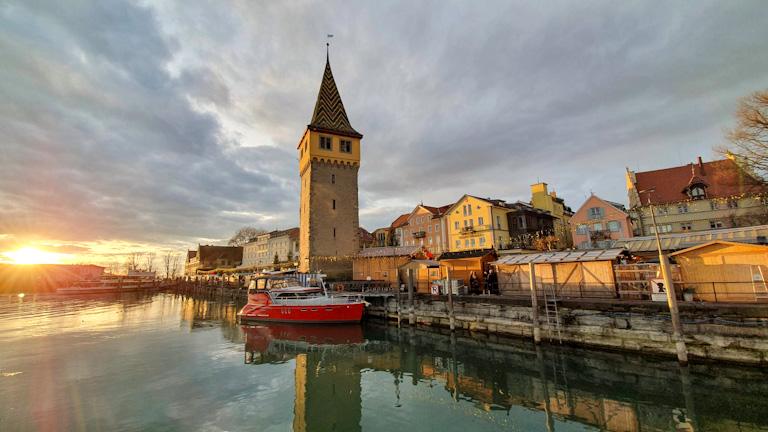 Sol se pondo no canto inferior esquerdo refletindo na água do pier onde no centro da foto se vê a torre alta e antiga de telhados coloridos, um barco pequeno ancorado e os demais prédios do porto