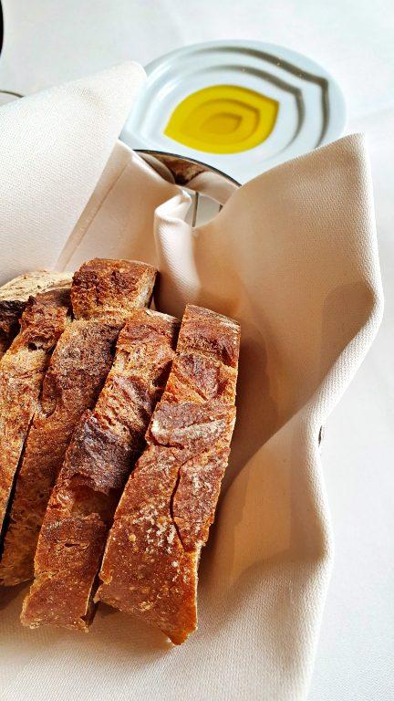 Aperitivos: pão artesanal com azeite e vinho branco em taça